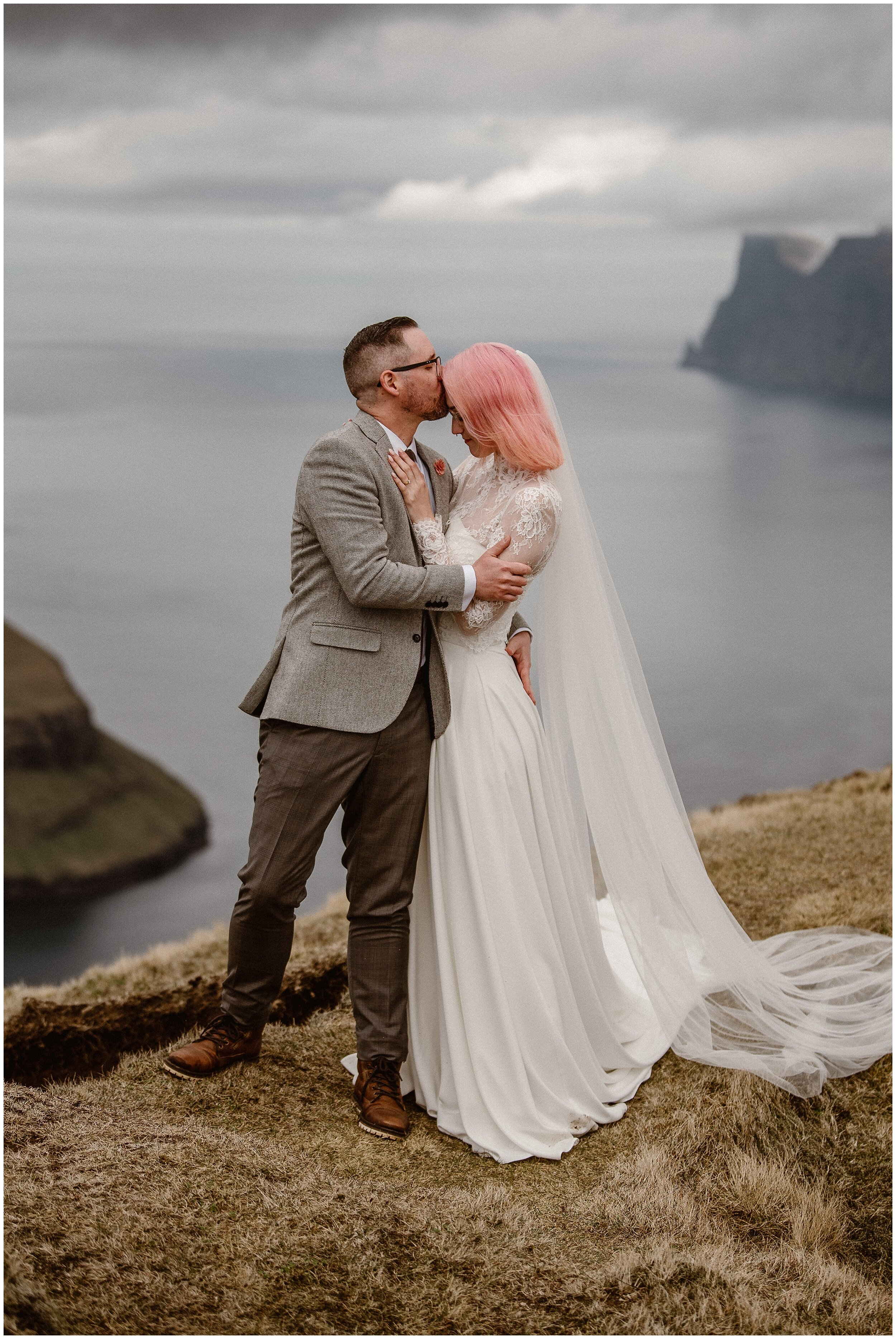 Elaura and Daryn, the bride and groom, hold each other close as they reflect on their adventure elopement day . Daryn leans in to kiss Elaura on the forehead, just below her pastel pink bangs. These adventure elopement photos in the Faroe Islands were captured by Adventure Instead, an elopement photographer.