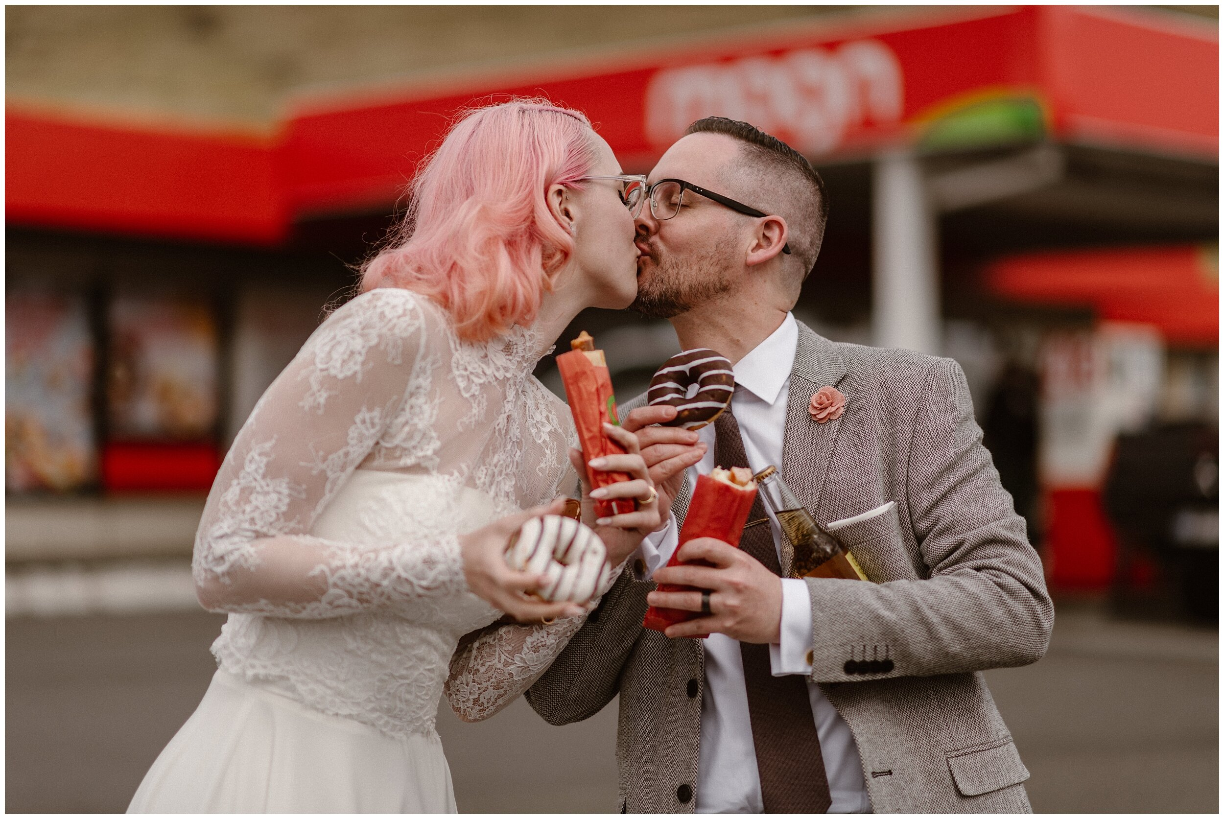 Elaura and Daryn hold gas station hot dogs in their hands (a Faroe Island must-have meal) as they kiss each other. The hot dog stop immediatley followed their hike down from the elopement ceremony and right before they head up for their second location for their elopement photos.