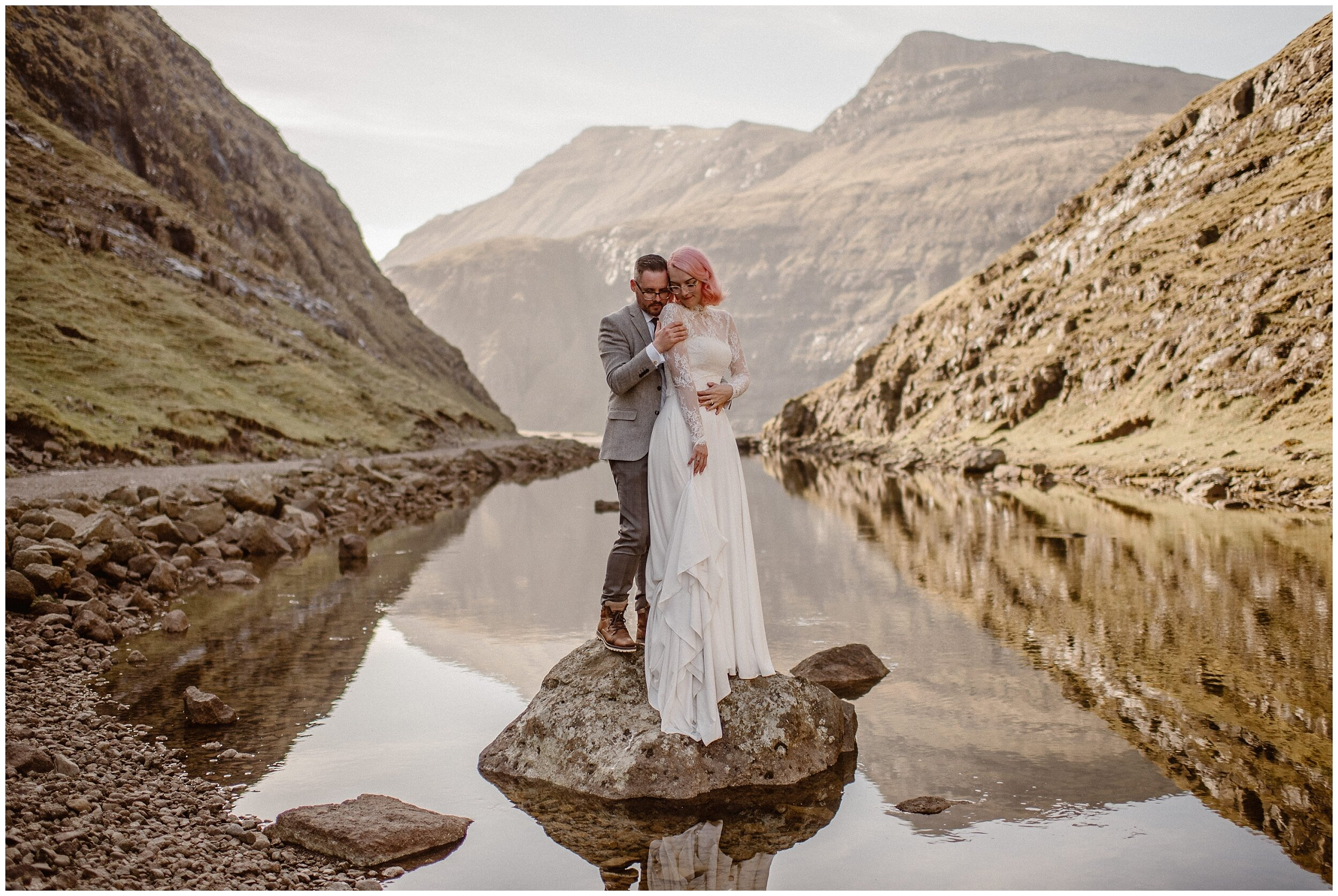 Elaura and Daryn stand up on a rock in a reflective lake as moutnains surroudn them. A gorgeous haze lays around the couple as they hold each other close in these adventure elopement photos captured by Adventure Instead.