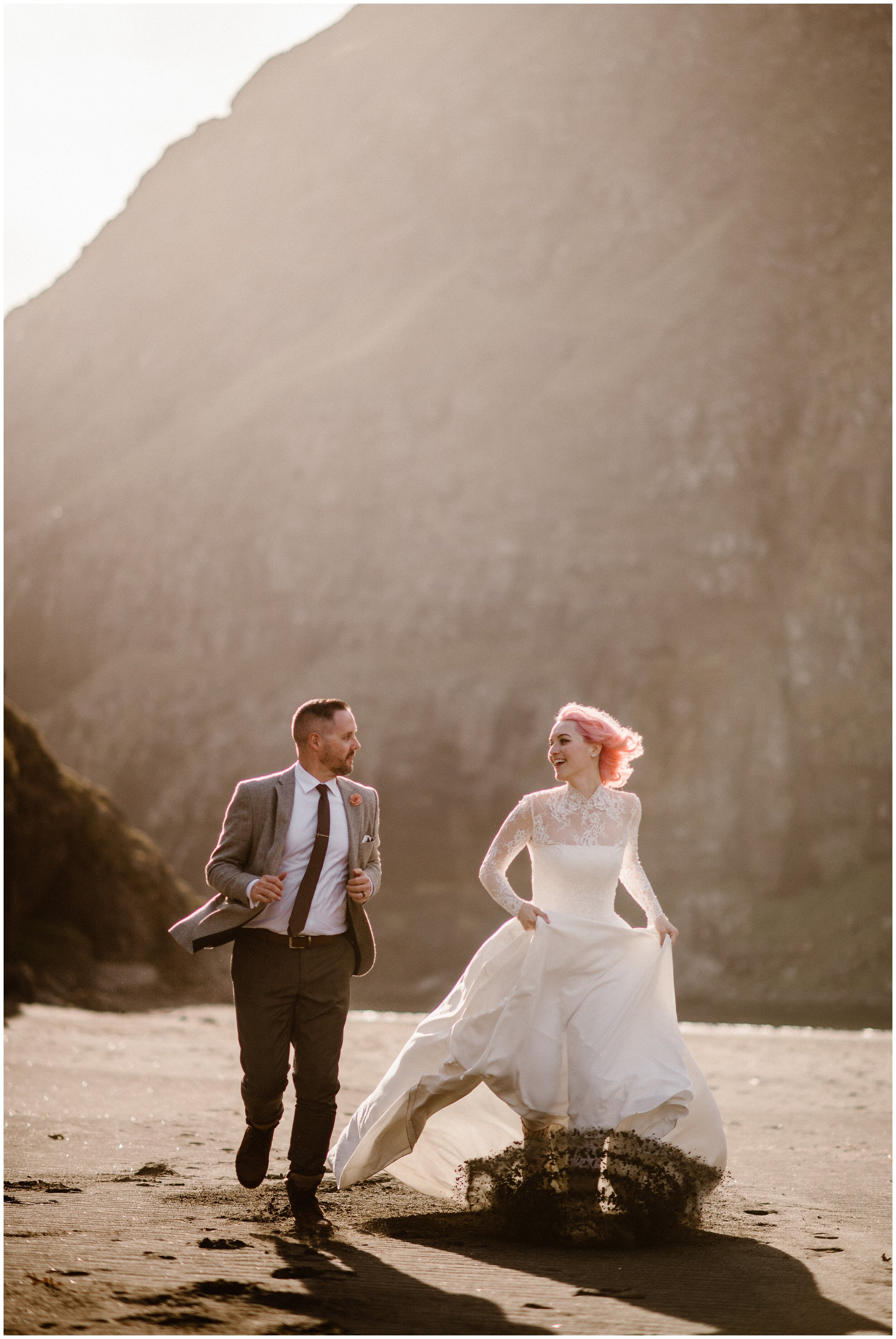 Elaura and Daryn run down a dark, sandy beach , staring at each other and smiling. Elaura's pink boots kick up a spray of dark sand, contrasting with her beautiful pastel pink hair. These adventure elopement photos were captured by Adventure Instead, and elopement wedding photographer.