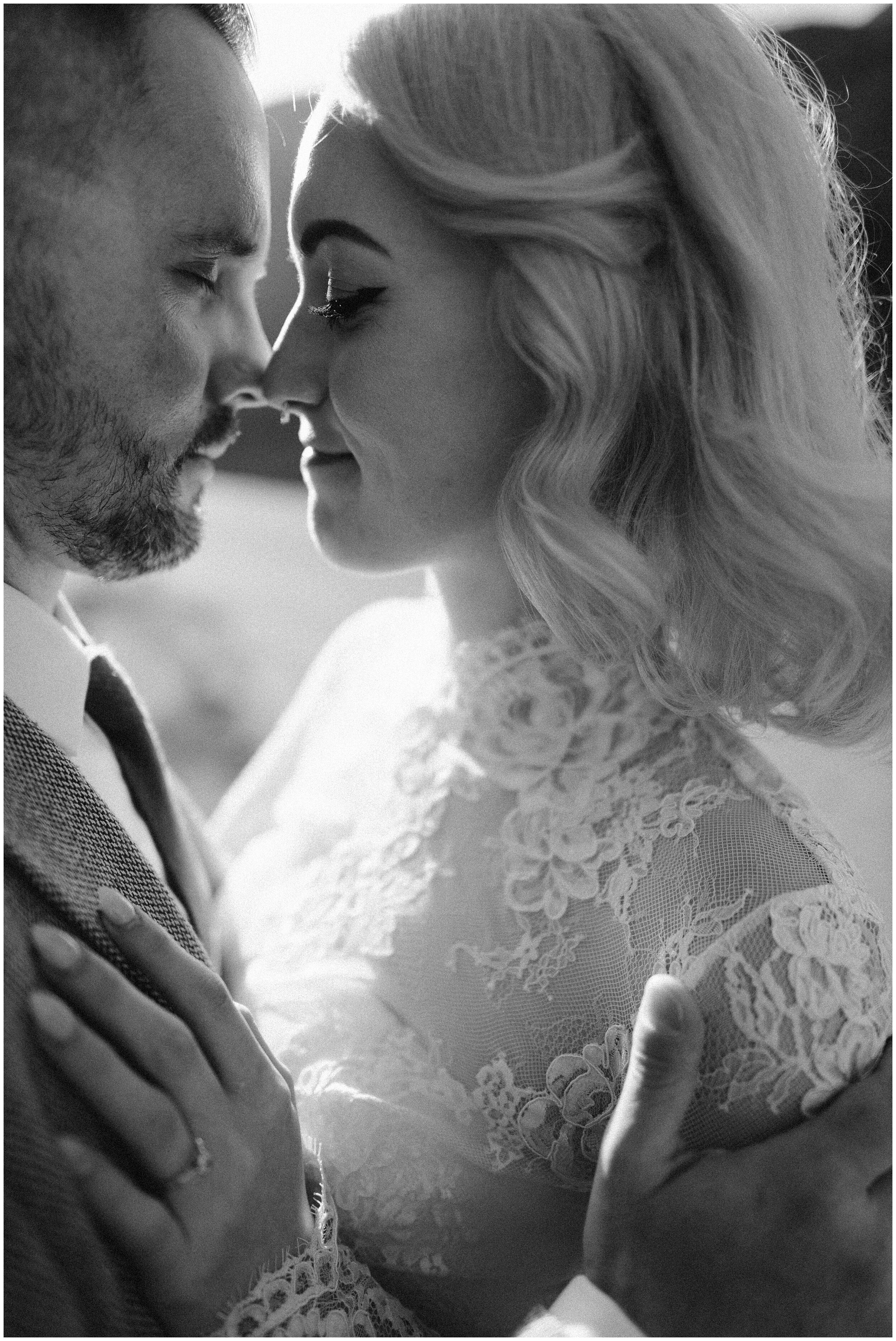 This photo shows a close-up shot of Elaura and Daryn, holding eachother close and looking into each others eyes. The details of Elaura's custom-made wedding dress can be seen up close in these adventure elopement photos shot by Adventure Instead, a destination elopement photographer.