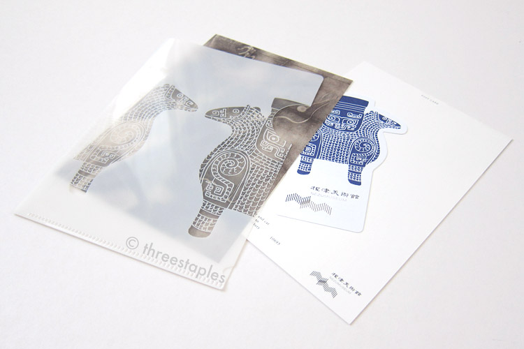 Small, white folder and postcards + museum ticket