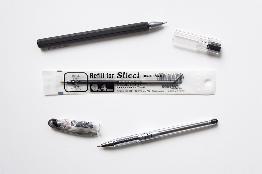 Uncapped: Muji (top) and Pentel Slicci in black (bottom), with Slicci refill 0.4mm still in its packaging in the middle.