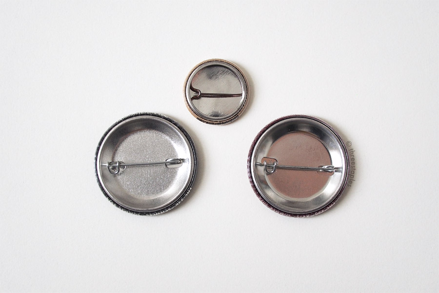 "Back sides, compared with 1"" button in the middle."