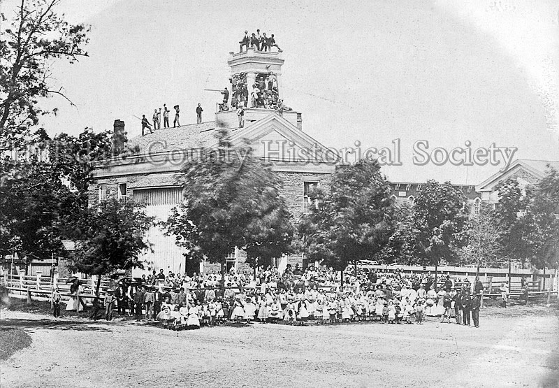 """Stone School on Courthouse Square on """"Moving Day,"""" when everyone helped to carry materials to the new Central School, where Bailey Elementary now stands."""