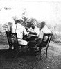 Men from  Little Italy play cards in the back yard