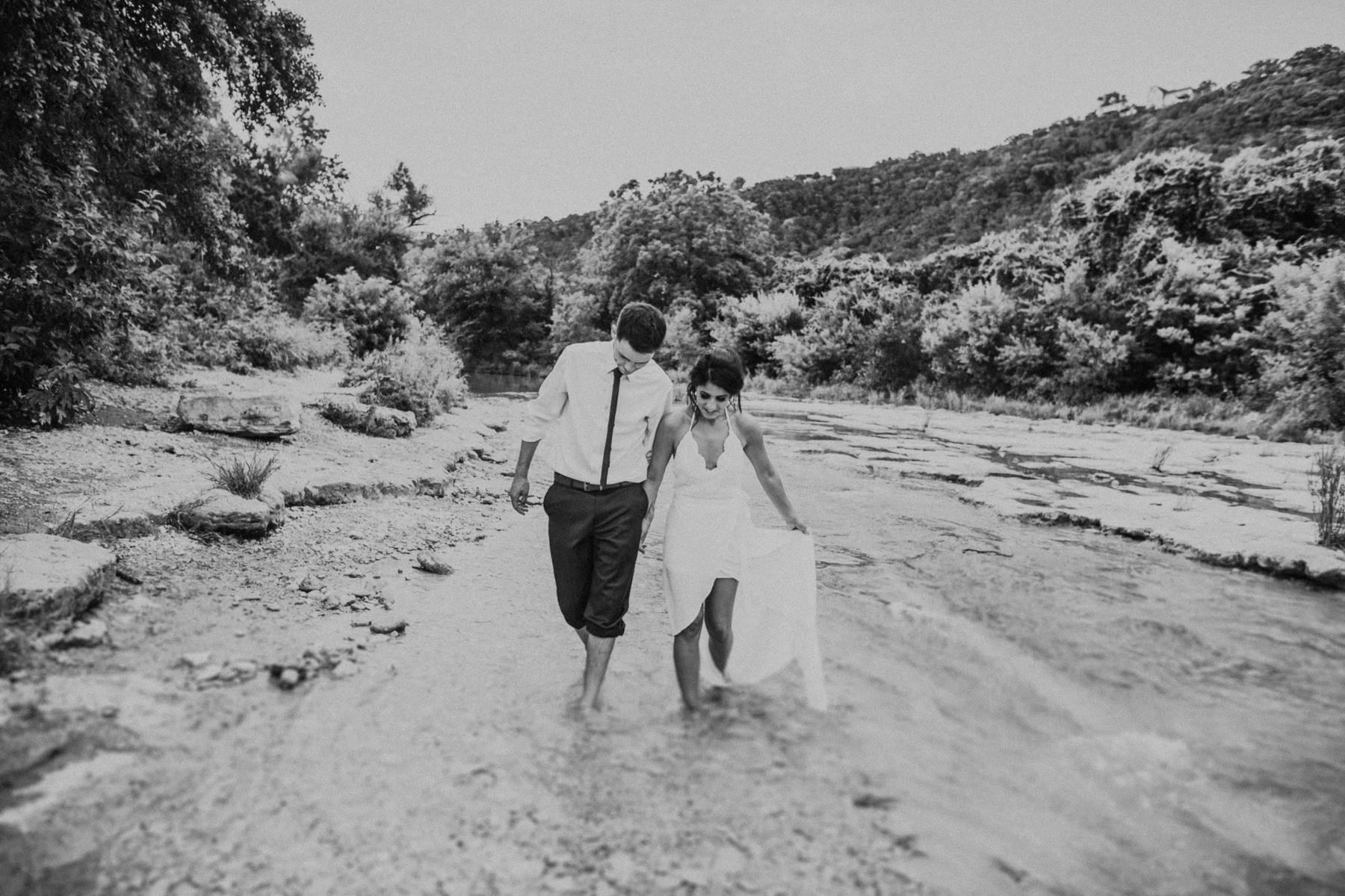bride and groom walking through water