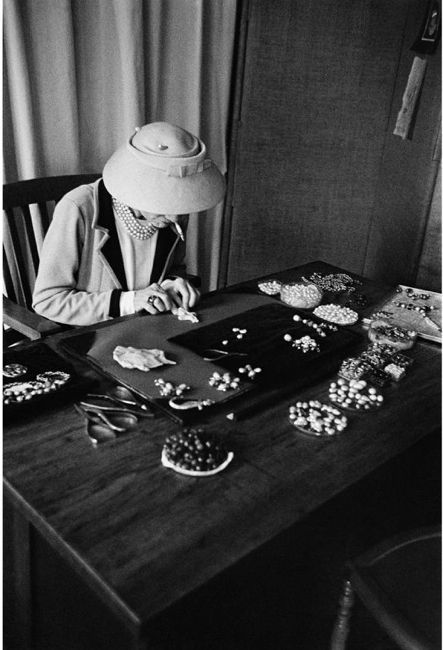 Coco Chanel designing her famous pearl necklaces.