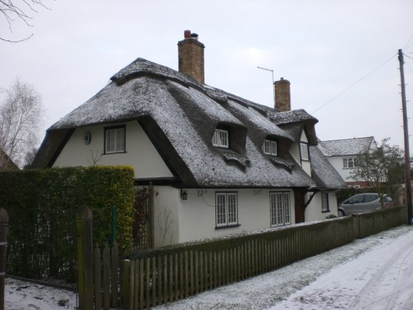 Thatched cottage, in the Fens during the big snow, Cambridgeshire, UK (Feb 2009)