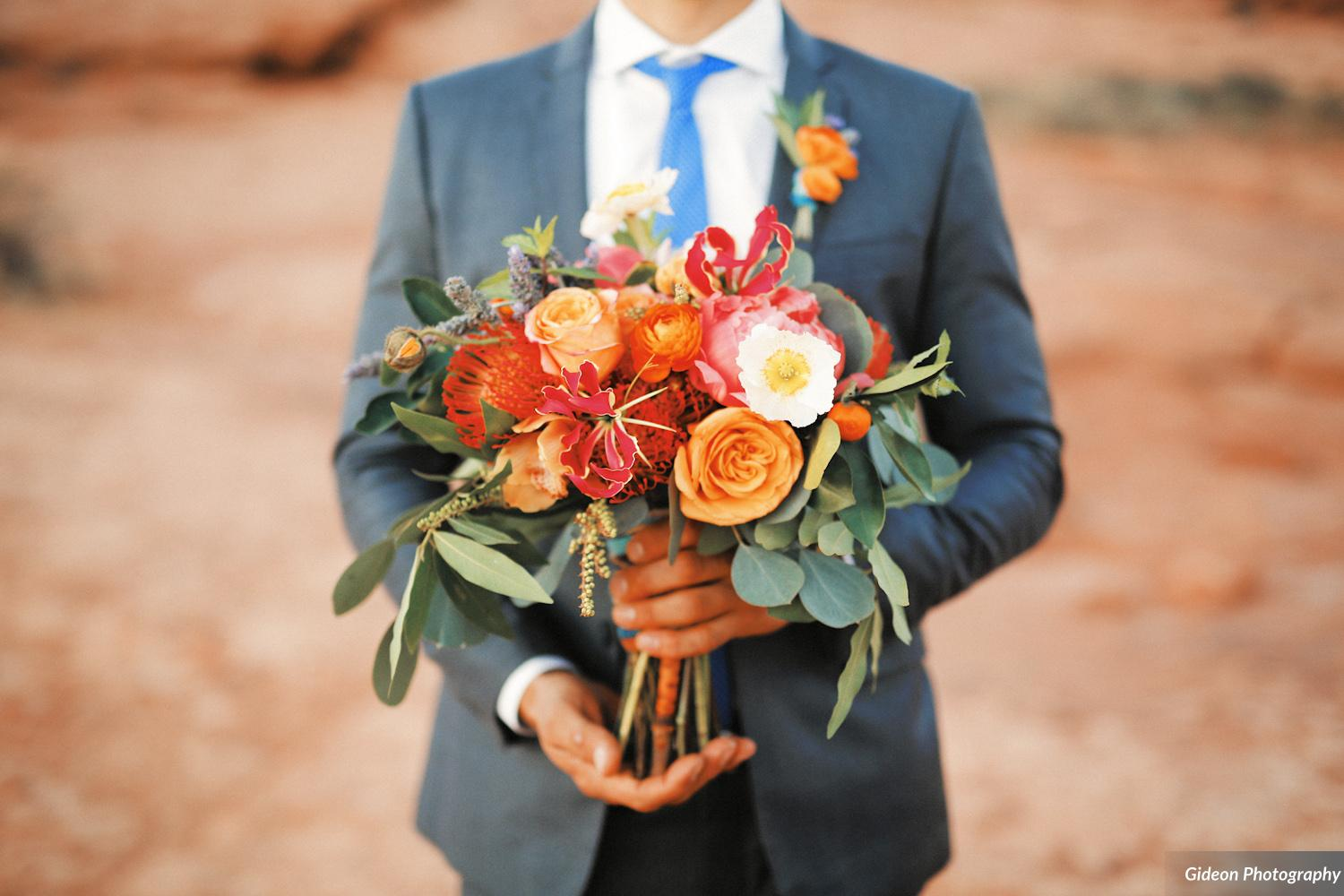 bridal bouquet with gold roses, coral peonies, anemones, gloriosa lilies, and protea