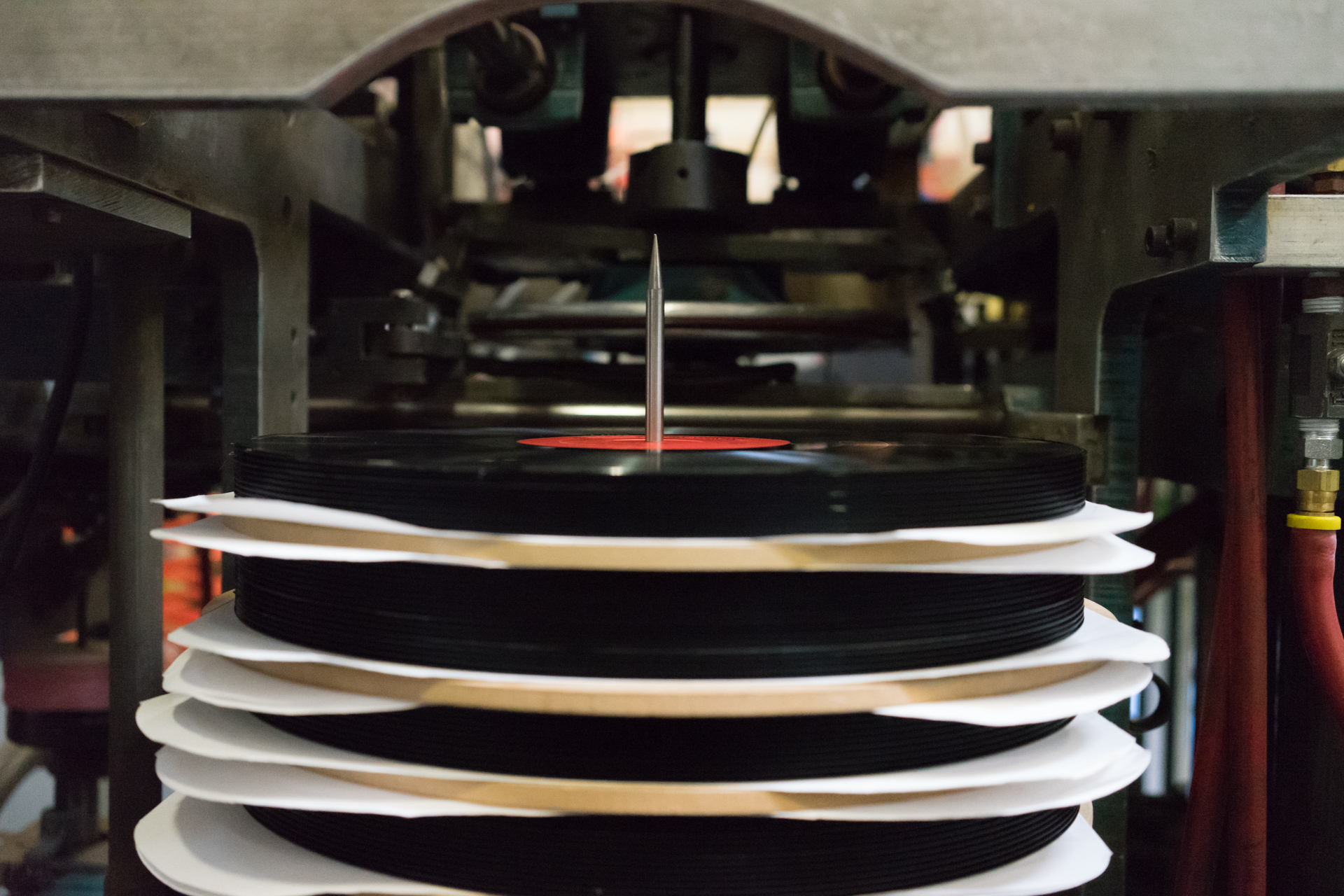 Pressed vinyl records are stacked to cool