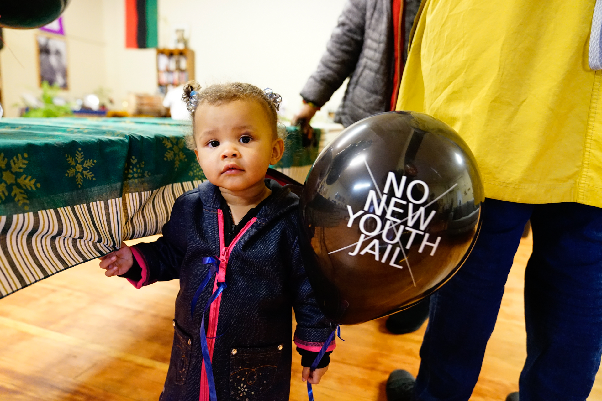 A young girl holds a balloon from the No New Youth Jail Campaign