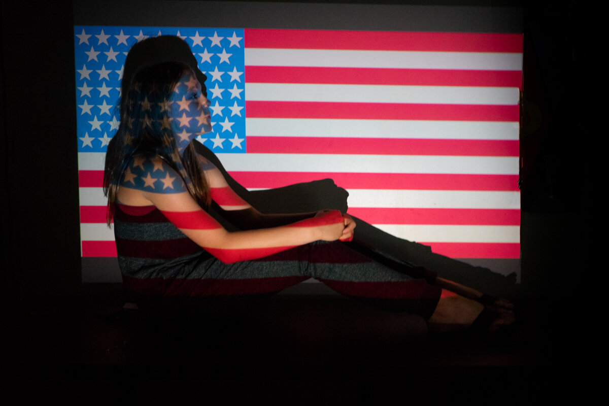 A MIDDLE SCHOOL STUDENT CHOOSES AN AMERICAN FLAG TO POSE AGAINST during an art and politics class.