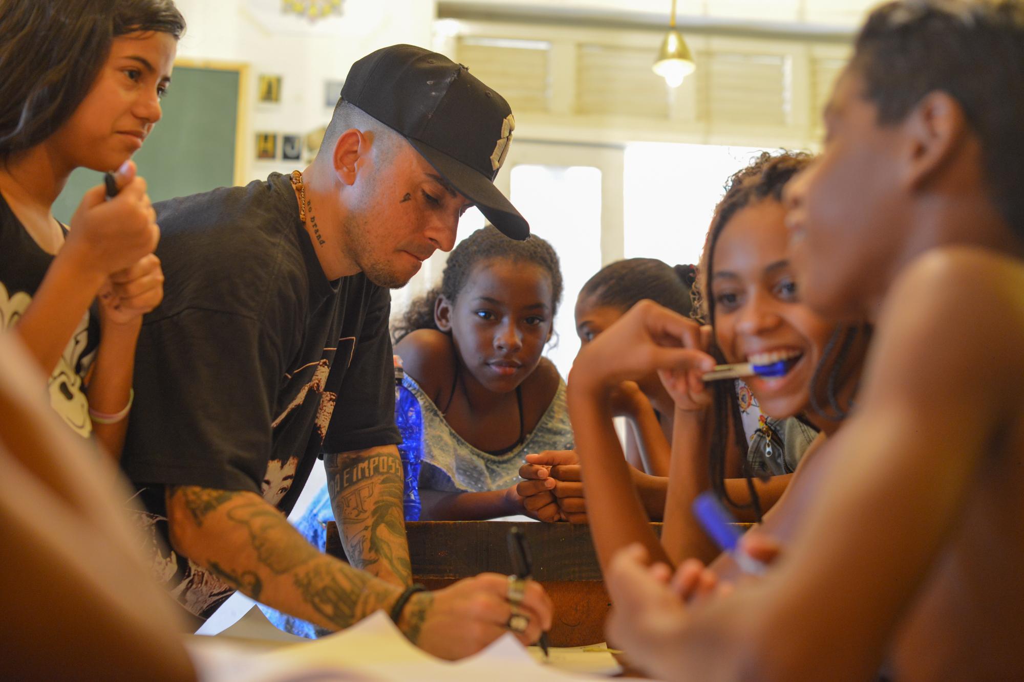 Daniel Shadow - Rap   Meu nome é Daniel Shadow, sou carioca, MC, produtor musical e trabalho há mais de 10 anos com Rap. Em 2007 fundei o Cartel MCs e produzi dois álbuns do grupo. Em 2010 fundei a gravadora independente Tudubom Records, produzi meu primeiro disco solo e dois álbuns do artista Filipe Ret. Na casa amarela, procuro passar pras crianças um pouco da minha experiência como MC e estimular a criatividade delas através de brincadeiras e jogos de palavras.