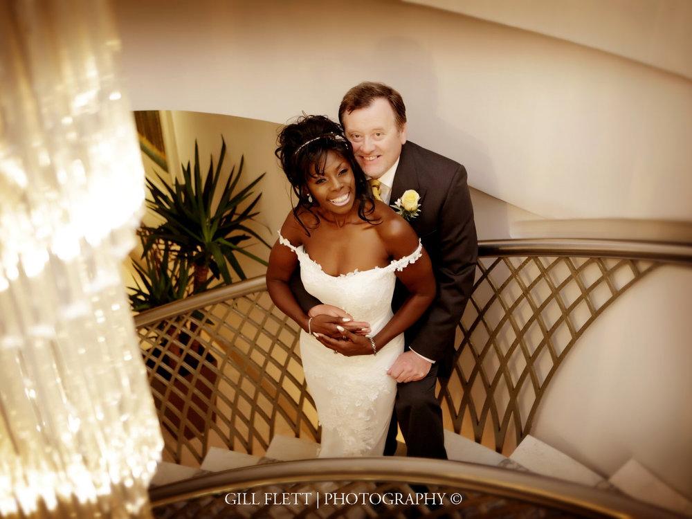 Chandelier-bride-groom-stairs-dorchester-ballroom-mature-interracial-wedding-gillflett-photo-london.jpg