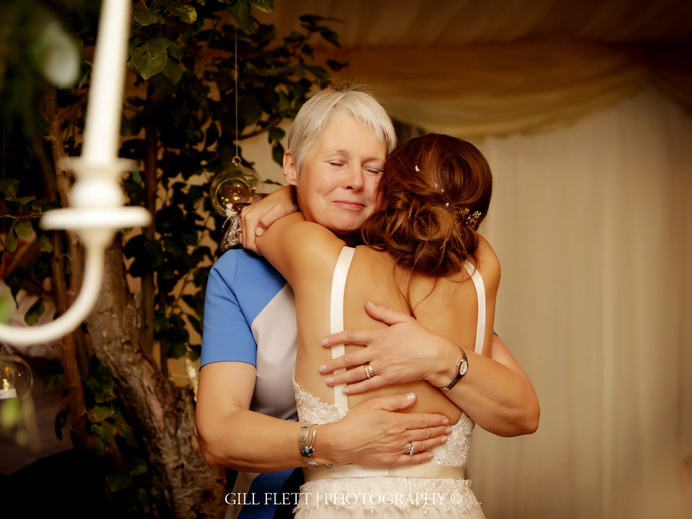 mother-cuddles-daughter-marquee-summer-wedding-gill-flett-photo.jpg