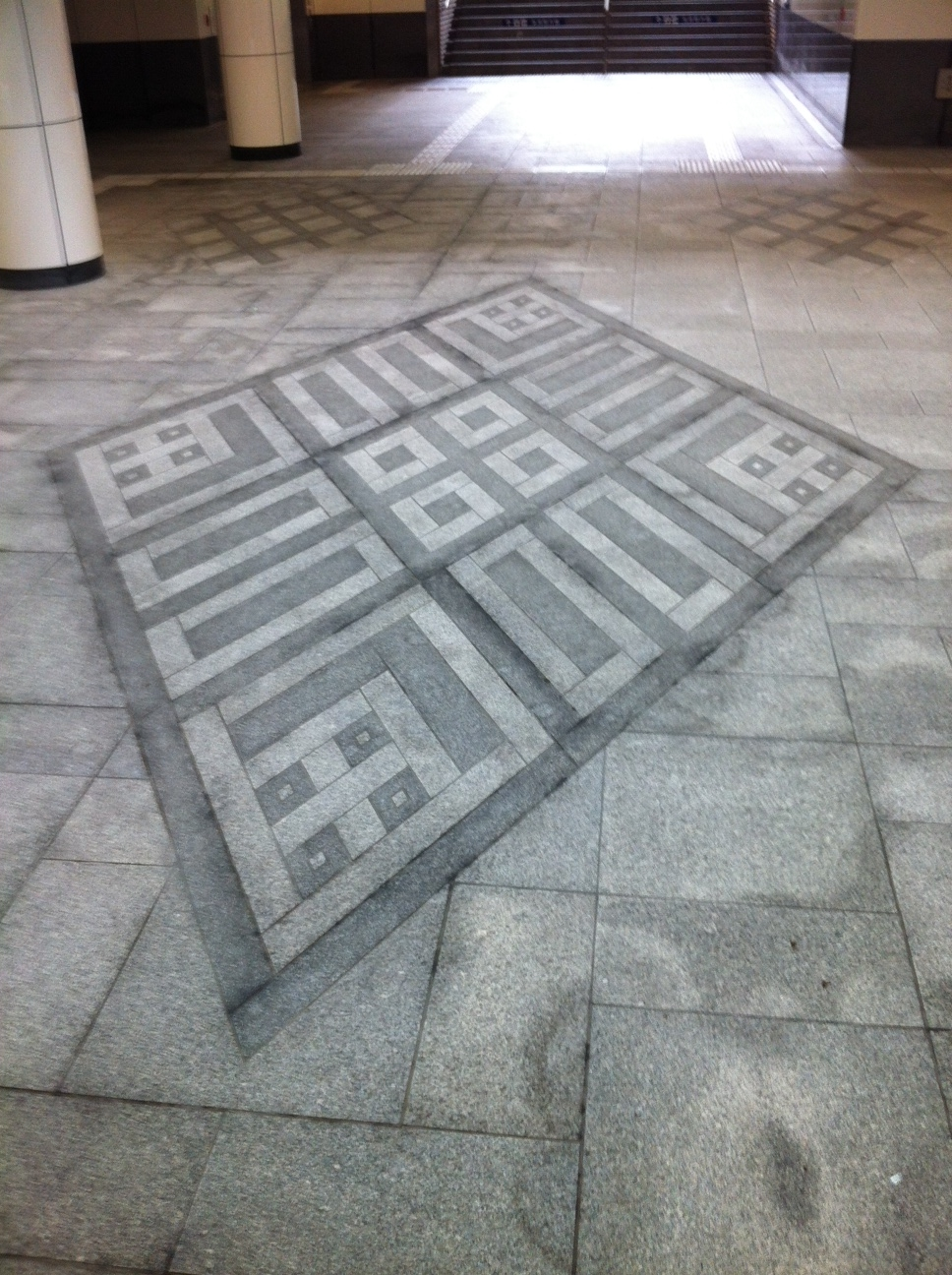 Koginzashi design on the floor of a tunnel that leads under an intersection in front of the train station.