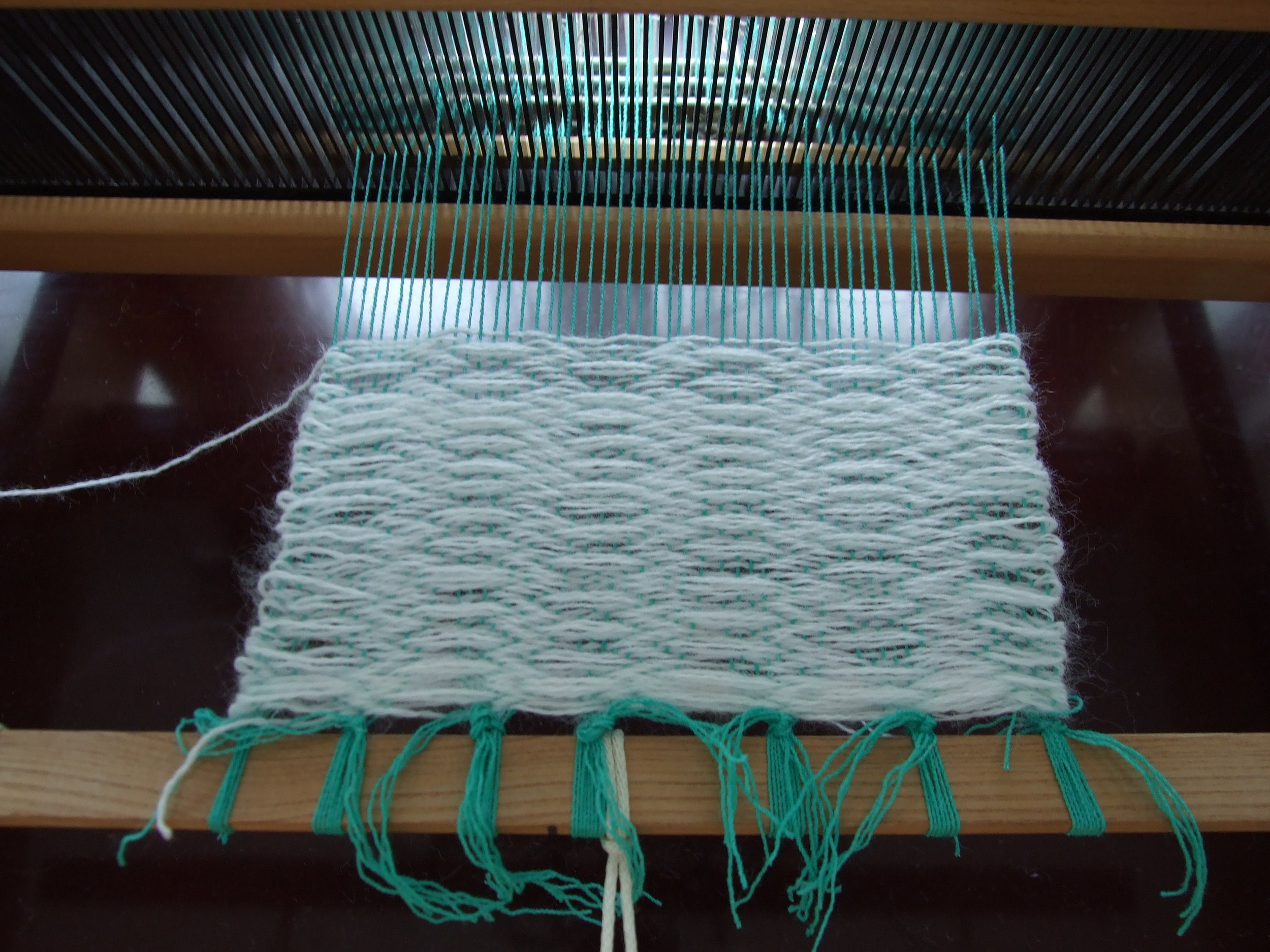 I'm having a little difficulty with the edges of the weaving but I've yet to consult the Youtubes for help. I am also starting to think that my reed slats are too wide for the thread I'm using. There was another reed with smaller spacing but I found out too late how to change them out.