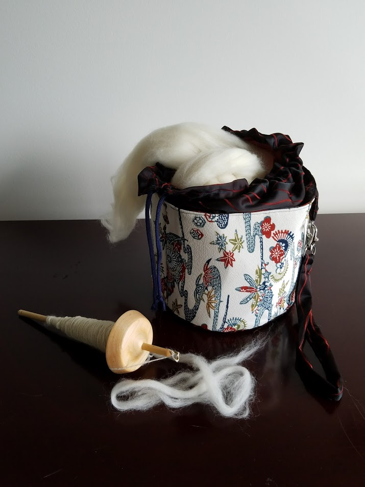 """This round project bag closes with a draw string top and has a detachable wristlet. It's perfect for a large knitting project or a giant ball of roving. 7"""" x 10"""" x 10"""""""