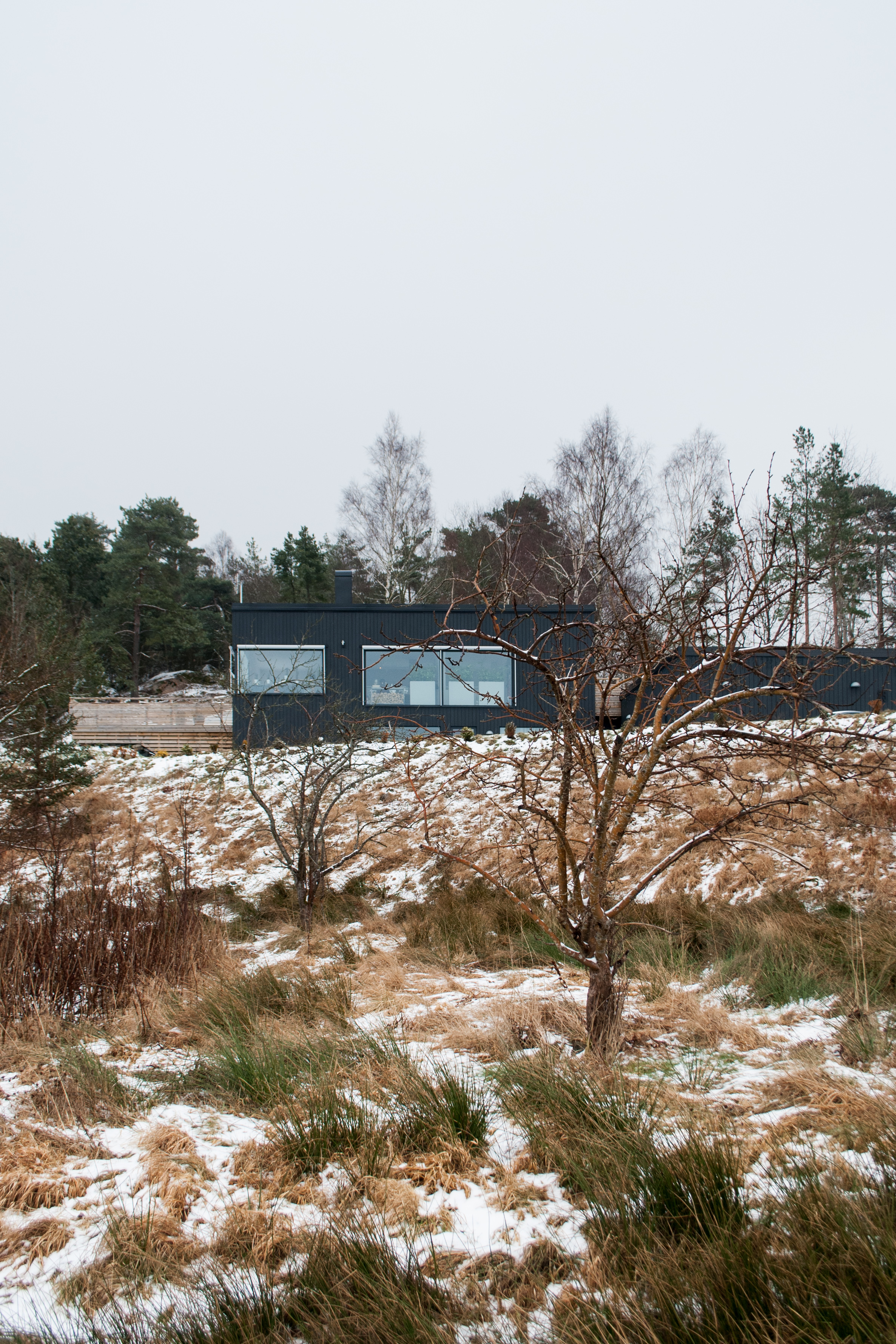 Situated on the outskirts of Gothenburg, this villa clings to a steep slope, incorporating the terrain within its layout. While at the front appearing large, clearly announcing itself from far away, the backside is low, private and cosy.