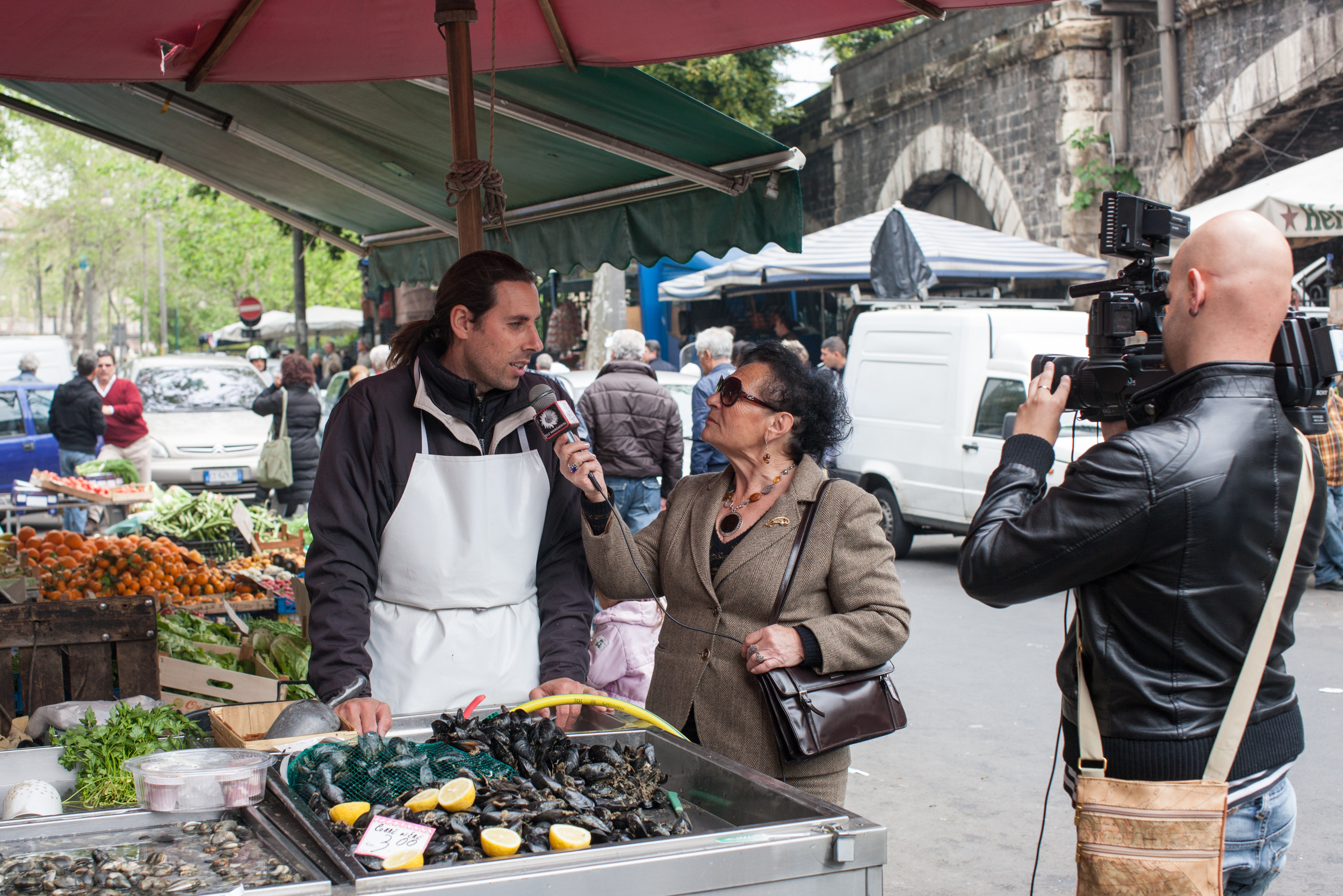 TV news reporter at fish market because it's Good Friday