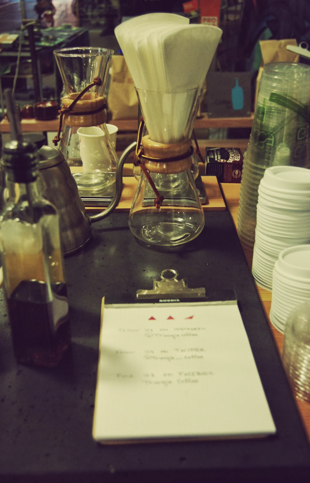 Chemex coffee makers (center) and other equipment is stored on top of or insidetwo coffee counter stands.