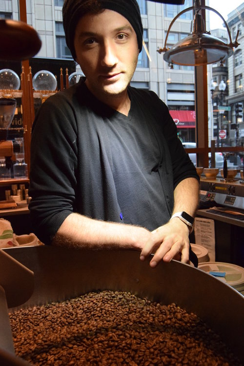 Anil Mezini, owner and founder of Jaho Coffee, stands in front of the roaster at his store's Chinatown location in Boston, MA.