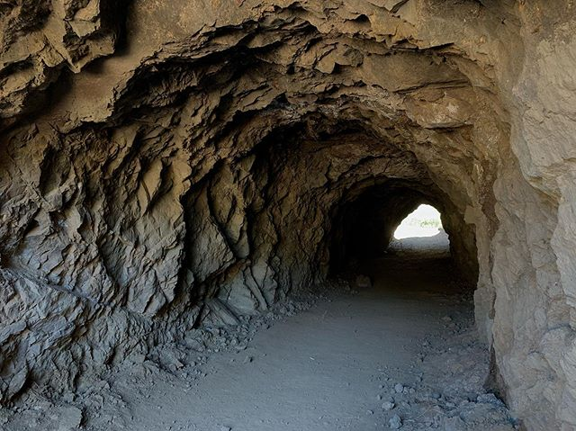 """Rags 2 Riches: Bronson Caves edition.  The Los Angeles Stone Company started around 1907 to help Los Angeles keep pace with booming growth and development. The Union Rock Quarry was placed in Brush Canyon to excavate the granite bluffs to become roads, hearths, chimneys and the infamous Hollywoodland not-so-secret stairs. It was crumbled and used for the Red Car tracks and can be found as far as the breakwaters of the Port of Los Angeles.  The quarry closed at the end of the 1920's and left behind the 200ft tunnels, now known as Bronson Caves, to LA's new fast-growing movie business. The caves were close to Hollywood and a short .3 miles from Canyon Drive although they looked remote and desolate on film. Soon enough, this blue collar quarry turned popular western and sci-fi film location.  Stars like John Wayne, Bela Lugosi and Natalie Wood had starring roles in movies filmed at the caves.  In the 1960's, a Lincoln Futura known famously as the Batmobile would drive through the tunnel and shoot out for the opening intro of TV Land's """"Batman"""" Series. And so it was, Bronson Caves became known as the Bat Caves. Jim Morrison took portraits here. The list goes on and on. What we know to be true is that this humble rock quarry has stones that became the literal foundation of LA and you can find them placed in all the far reaches. It's walls became the face and backdrop for hundreds of television and movie locations. And when everyone goes to bed, the owls and coyote call it home."""