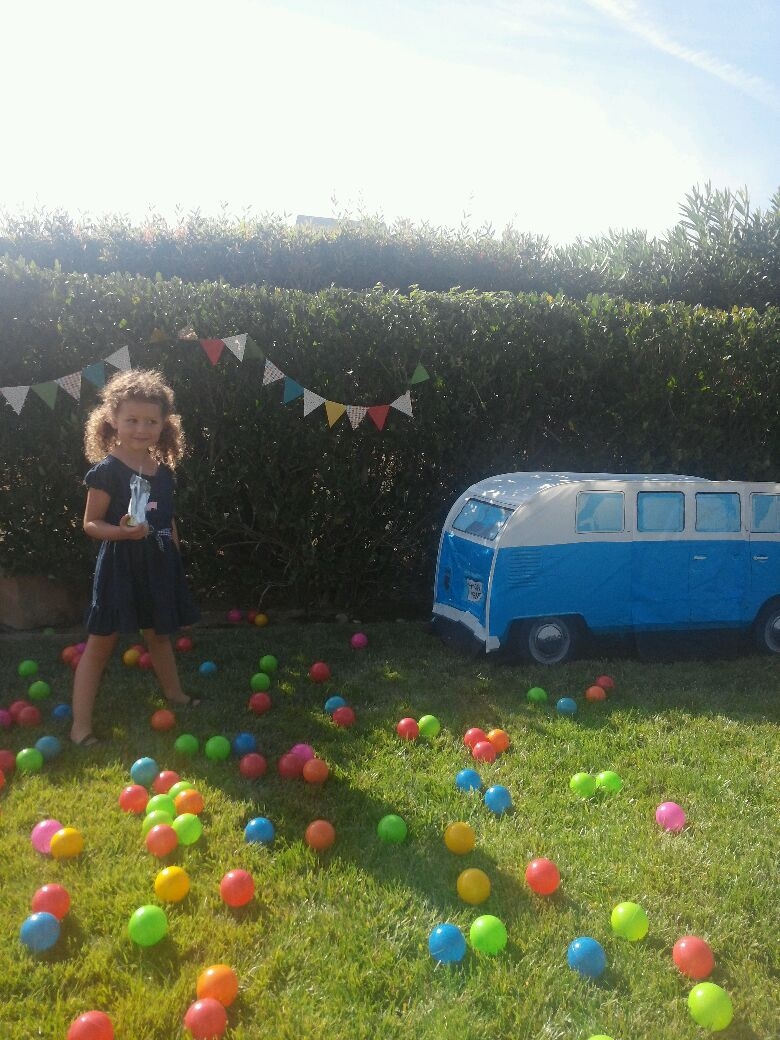 The always adorable Evia (our forever flower girl at our wedding) posing for the camera. The VW tent and pit balls were a huge hit with the kiddos! --Photo via her mama Jess.
