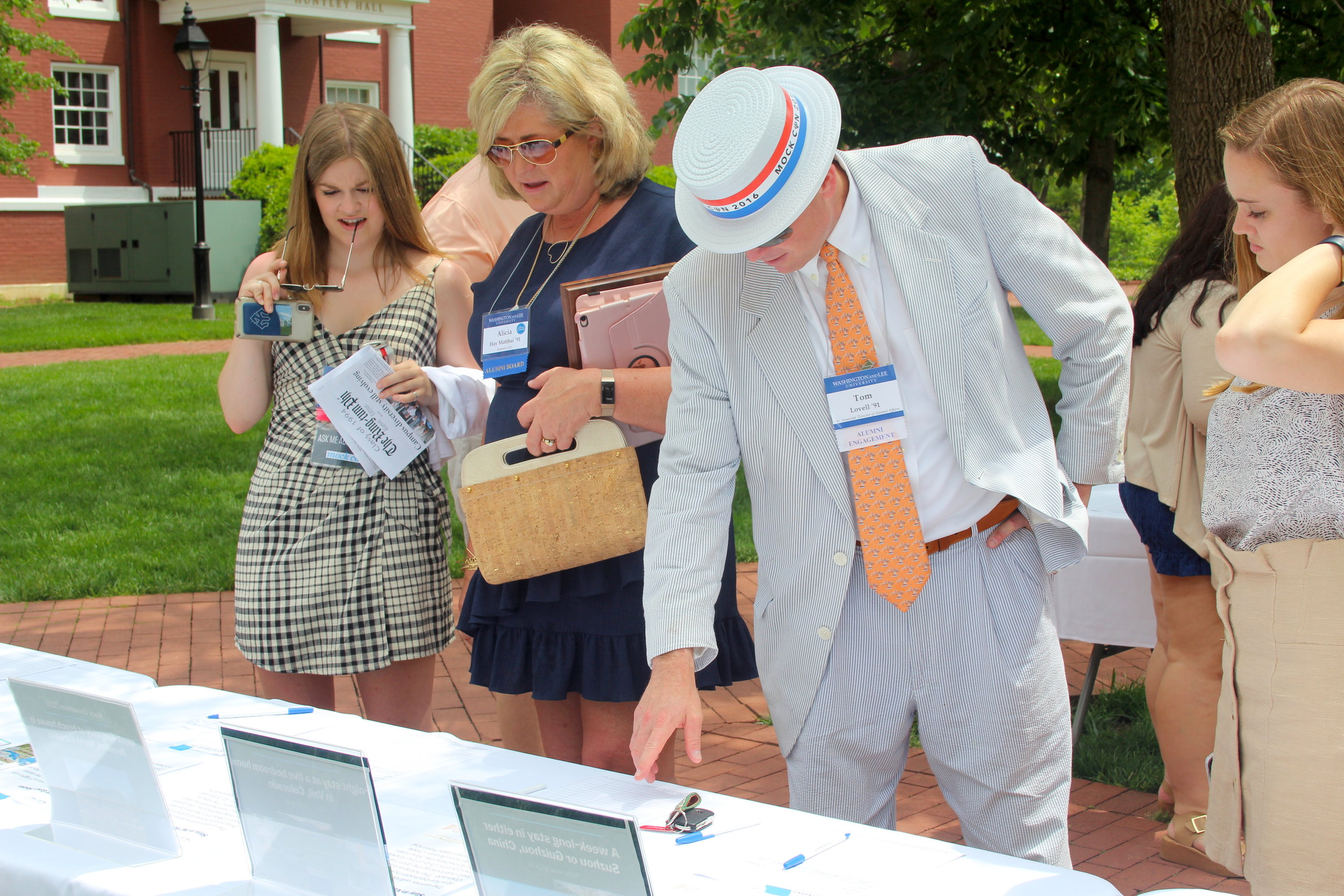Two alumni peruse Silent Auction items, assisted by General Secretary Layne Smith '20 and Financial Chair Elizabeth Thompson '20.