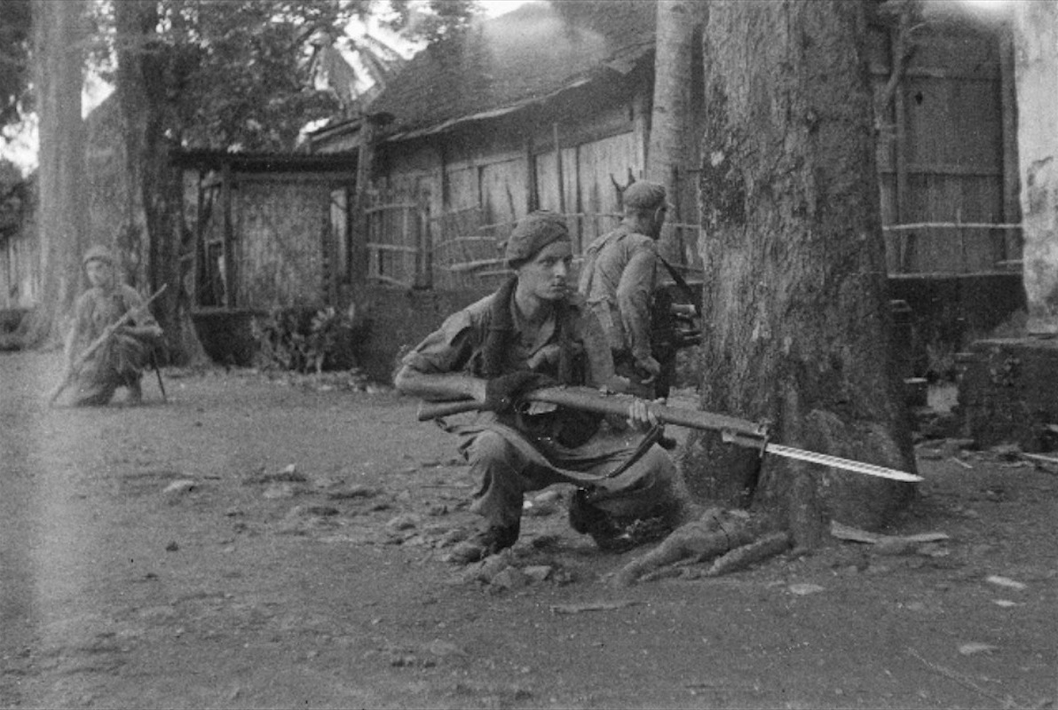 Brigade V memasuki Surakarta Jawa Tengah saat agresi militer Belanda kedua. Di latar depan nampak serdadu wajib militer M.A.P de Lange berpose sesuai permintaan juru poto agar bayonetnya nampak berkilat oleh sinar matahari. 21 Desember 1948.