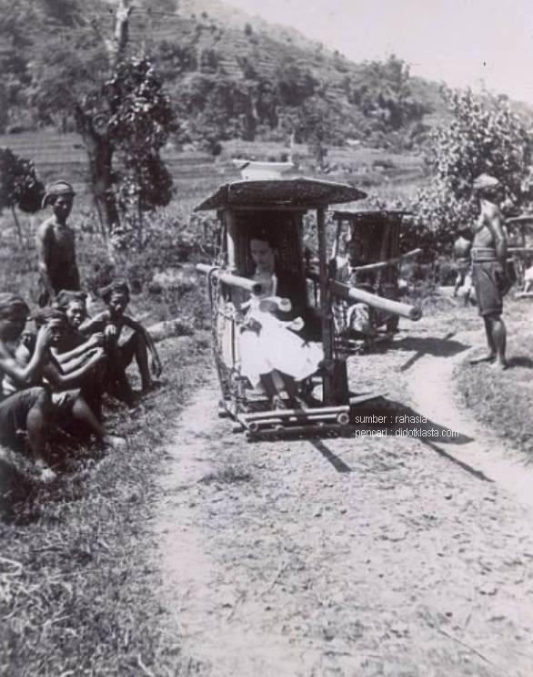 Perempuan kolonial dan baboenya di atas tandu sedang istirahat dalam perjalanan dari kawedanan Grabag (sekarang sebuah kecamatan di kab. Magelang) ke Hotel Merbaboe di Magelang gemeente (kota swapraja). Sementara bumiputra kuli penjunjungnya pada jongkok di tepi jalan. ca 1922.