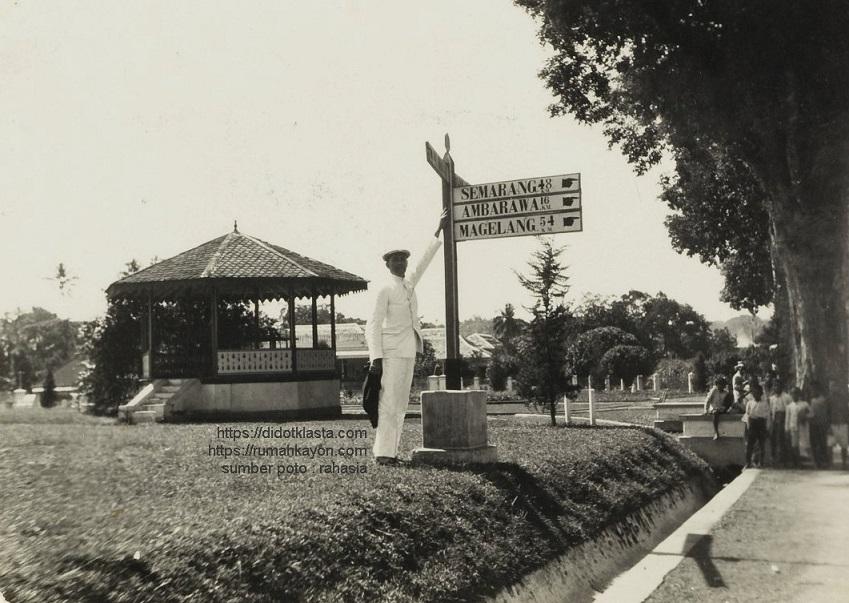 Mener Meyer sedang berdiri di dekat plang penunjuk jalan. Melihat nama-nama kota dan jarak tempuhnya, dugaanku ini di tempat yang sekarang dikuasai Ramayana Mall, eks lapangan Tamansari, eks Kerkplein (lapangan gereja). Mener Meyer sendiri adalah keturunan tentara dari Afrika di India. Antara 1930 - 1935.
