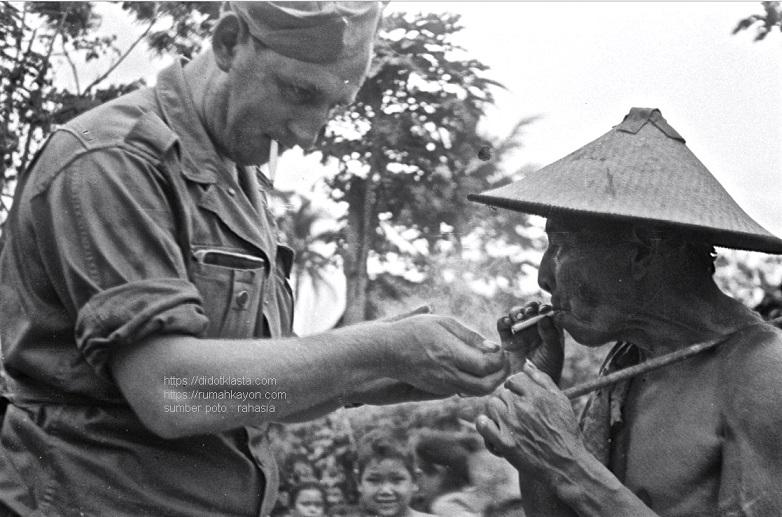 Serdadu Smulders dari Tilberg Belanda menyalakan rokok Charles Bronson, rakyat petani Salatiga. 8 Oktober 1947.