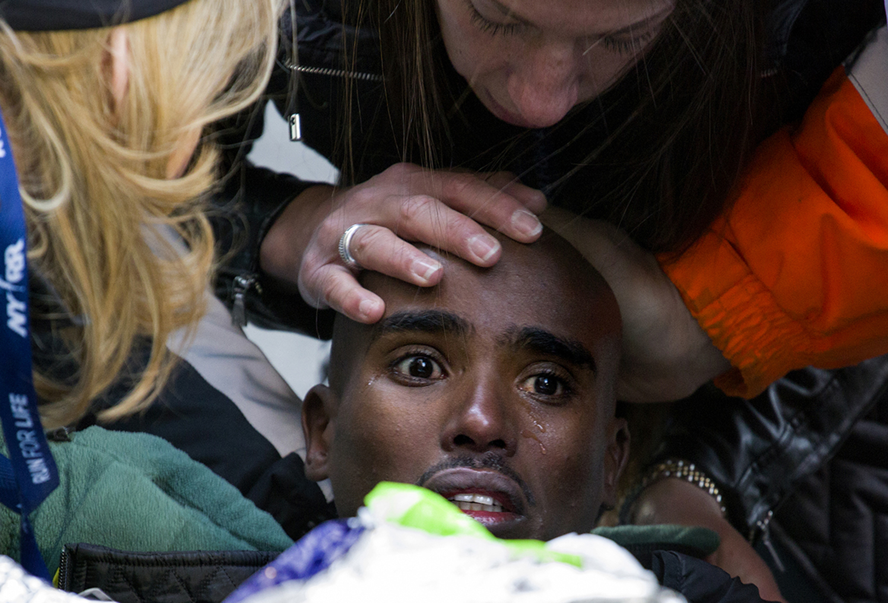 Mo Farah of Great Britain is comforted after collapse, New York Half Marathon (recovered soon after), 2014