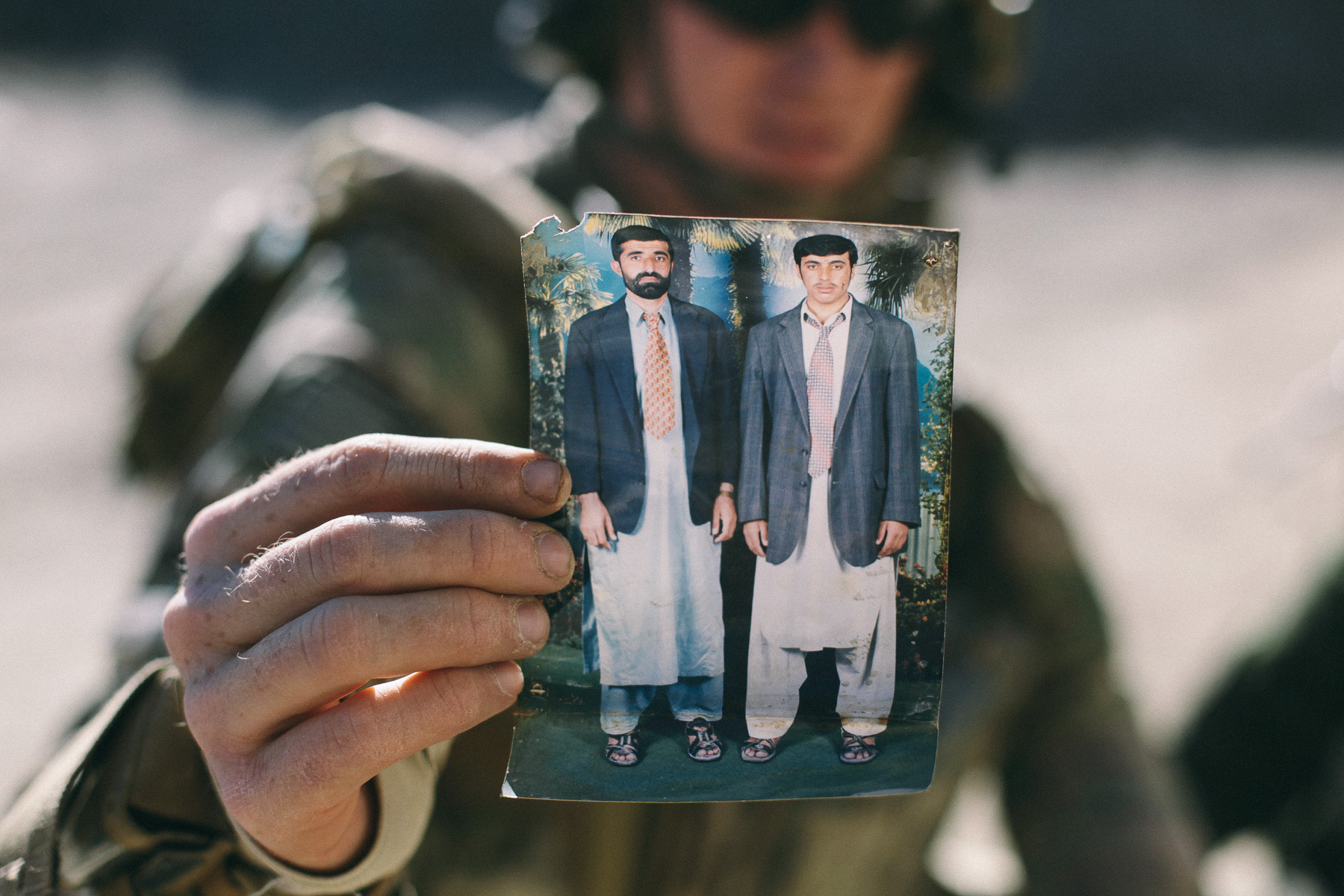 Member of a US Provincial Reconstruction Team holds up a photo highlighting a mix of Afghan and Western dress found in an abandoned village. Travelers in the area reported that people left the village due to a combination of poor farming conditions, bad roads, and harassment by insurgent and coalition forces.