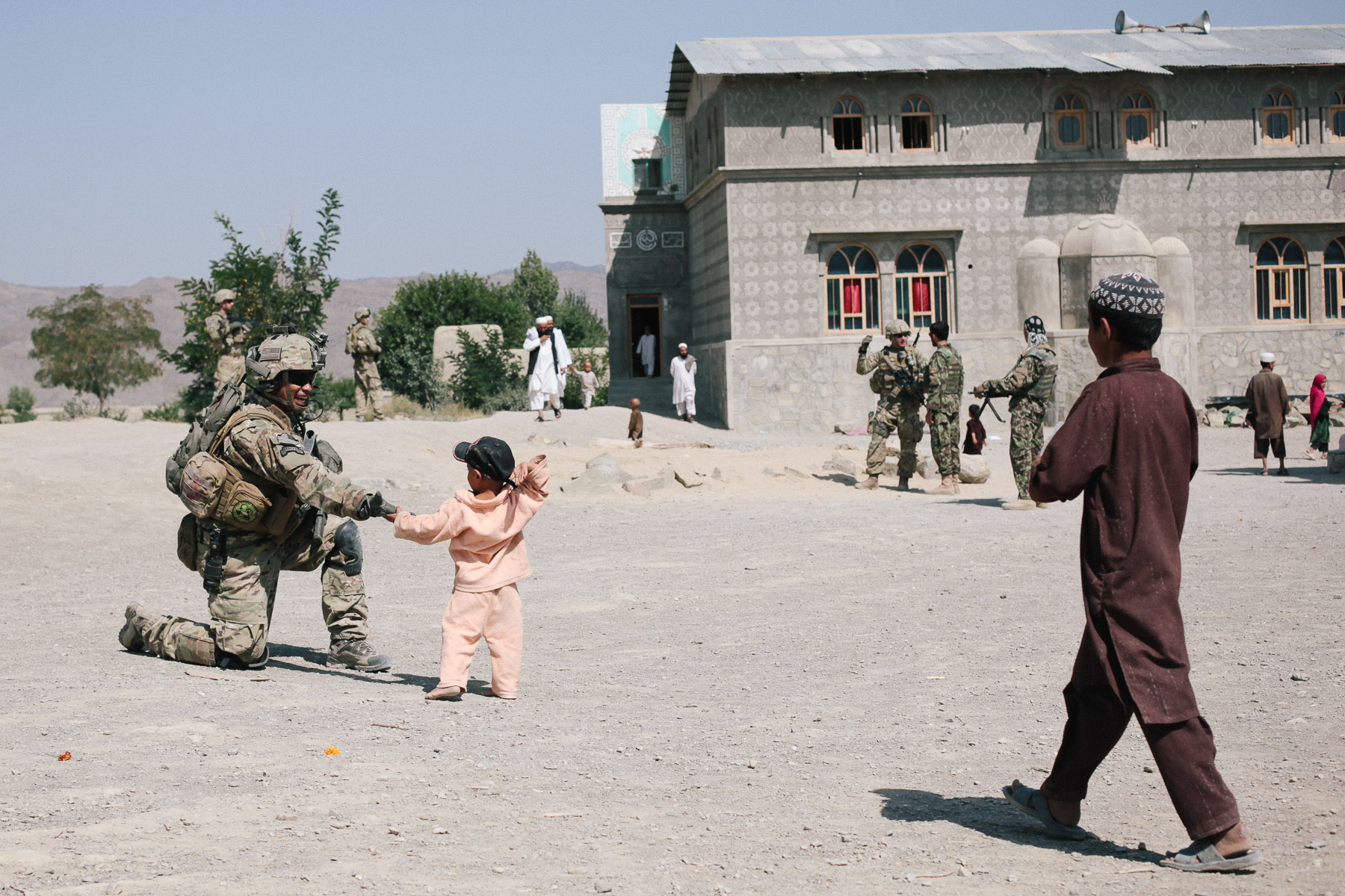 "A member of the Provincial Reconstruction Team's Security Force gives a local child a ""low five"" while the PRT assesses a primary school for possible repairs."