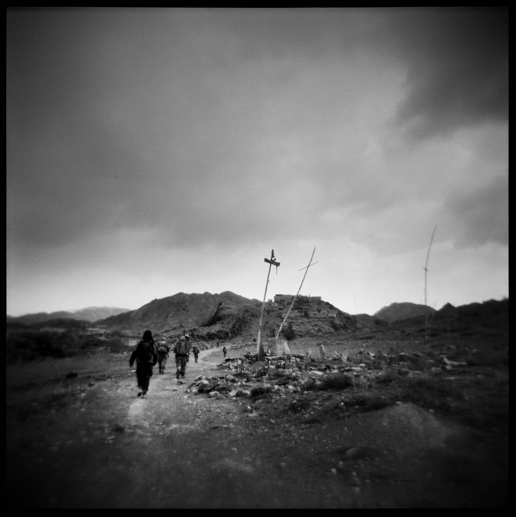 Soldiers pass a local graveyard while on patrol in the Gayan Valley. Paktika, 2011.