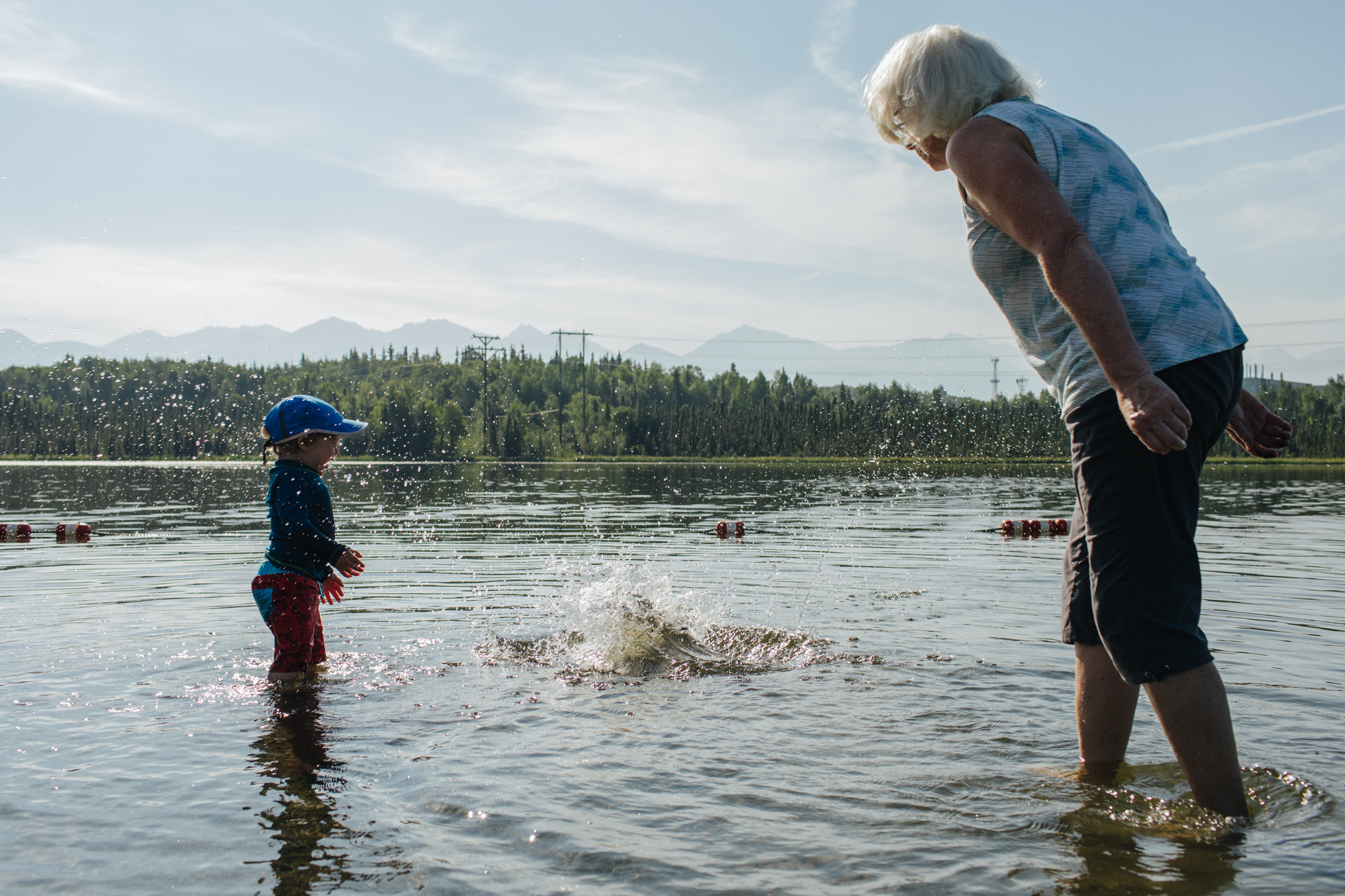 Robin Nyce (r) plays with 19 month old Fischer Nyce at Goose Lake in Anchorage, Alaska during an abnormal, prolonged heatwave. For The New York Times.