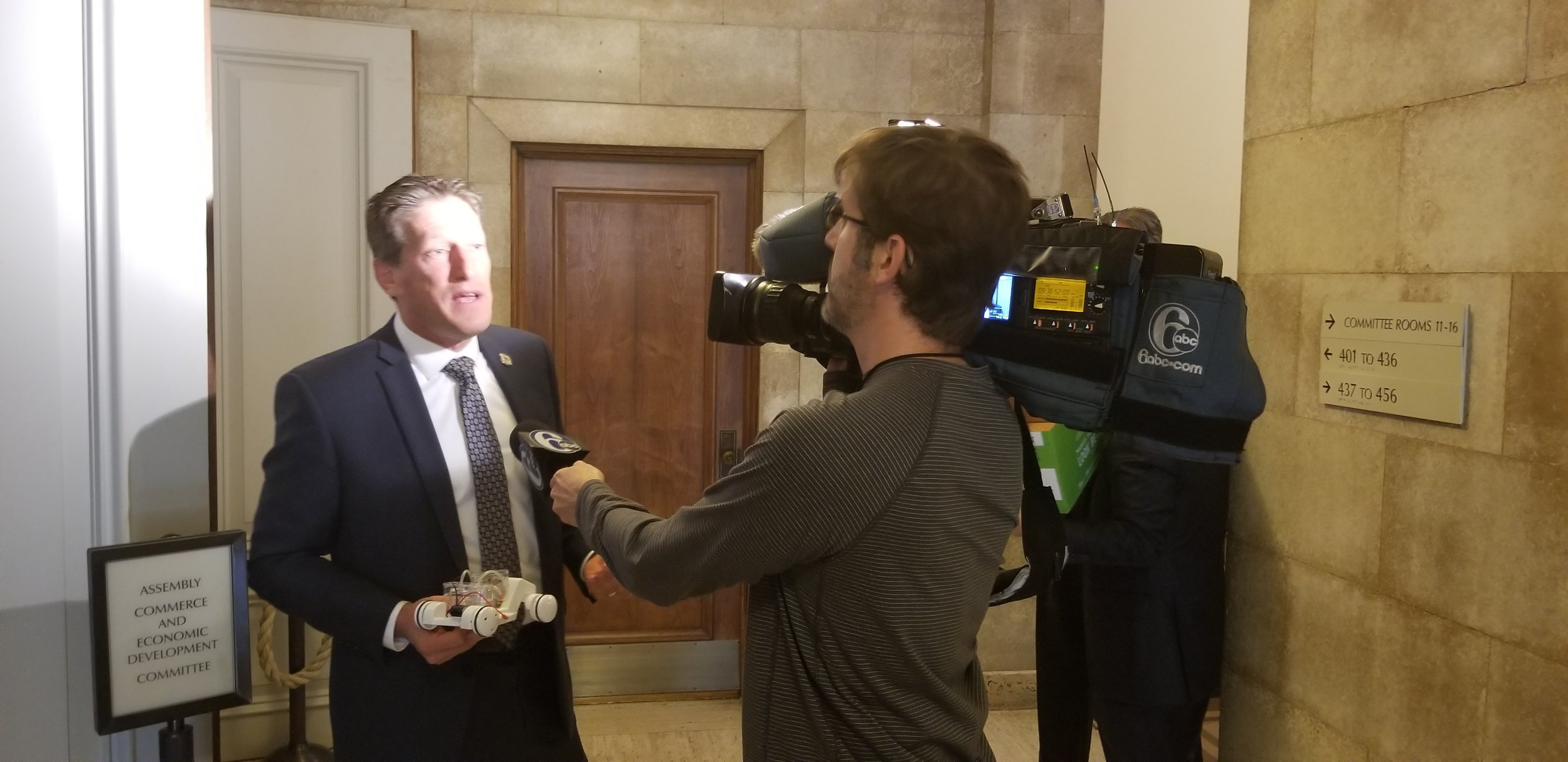 Assemblyman Andrew Zwicker (left) discusses hydrogen fuel cell transportation with a local ABC news affiliate.