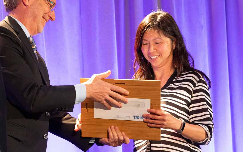 NREL Director Martin Keller presents Huyen Dinh with an NREL Staff Award in March for her achievements. Photo by Werner Slocum, NREL