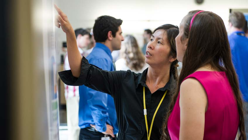 In 2013, NREL intern Erin Brahm (right) explained her research poster to Huyen Dinh at a poster session. Photo by Dennis Schroeder, NREL