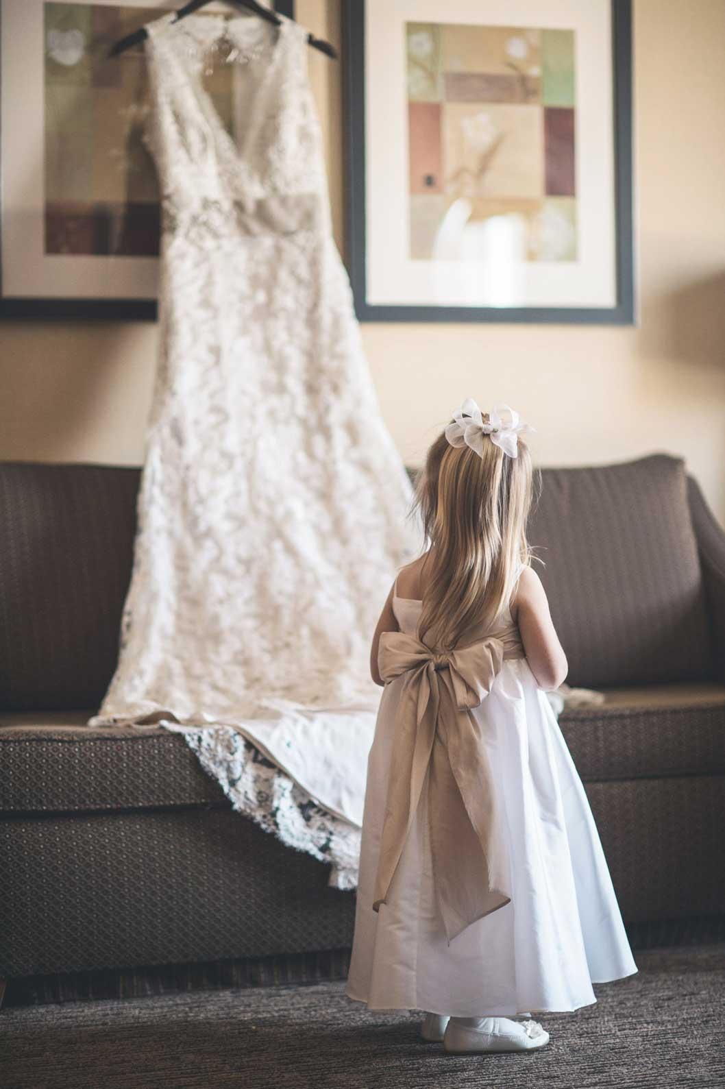 Flower girl looking at bride's dress