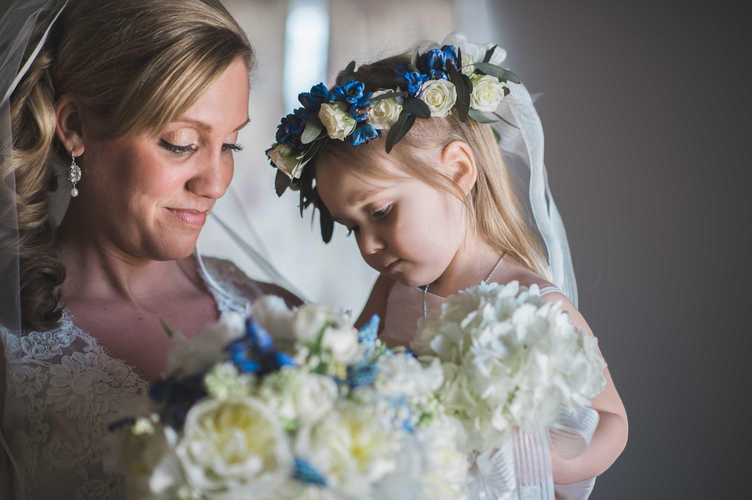 Flower girl smelling bride's flowers