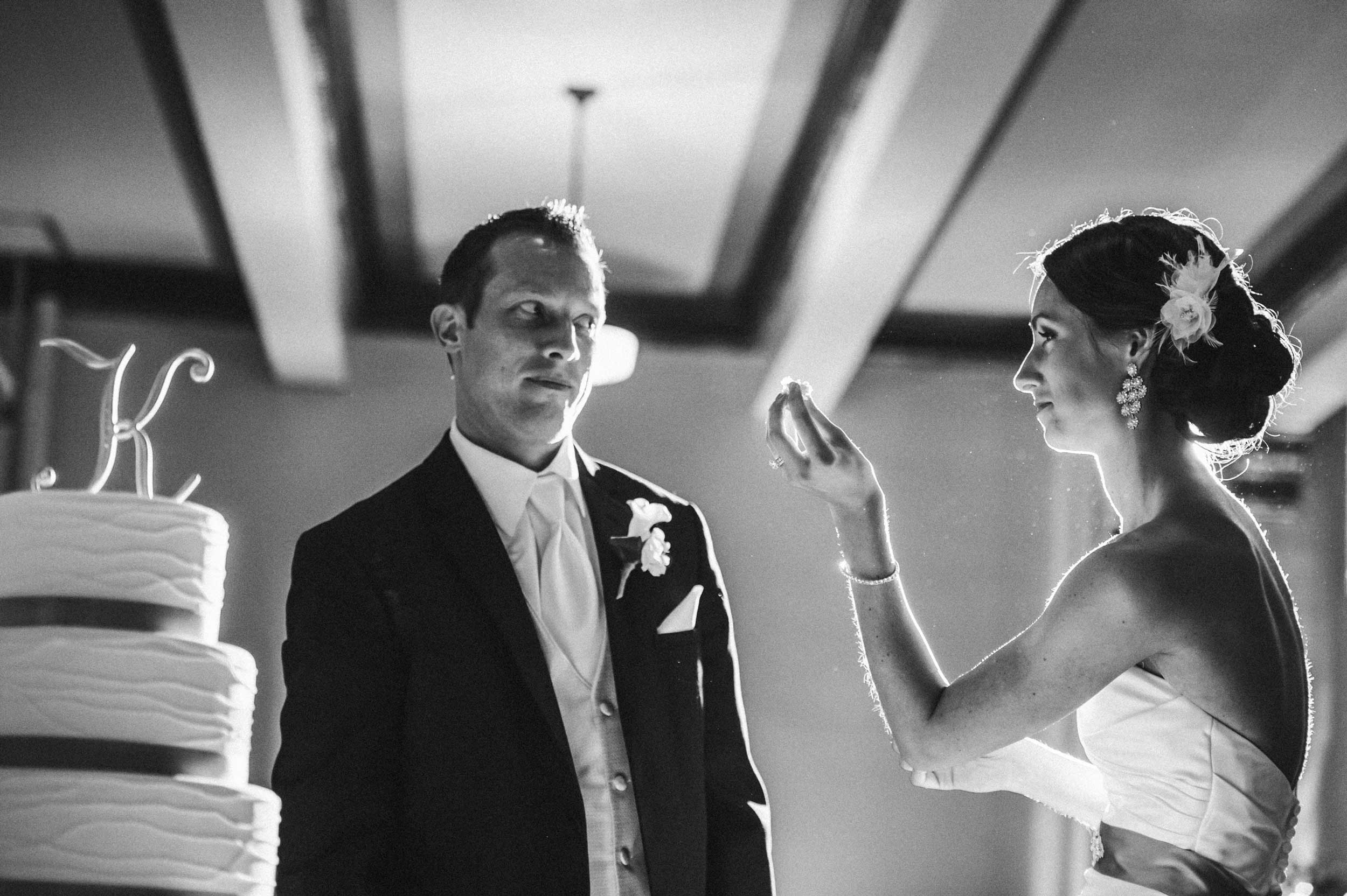 Groom giving the bride a warning look as they cut the cake