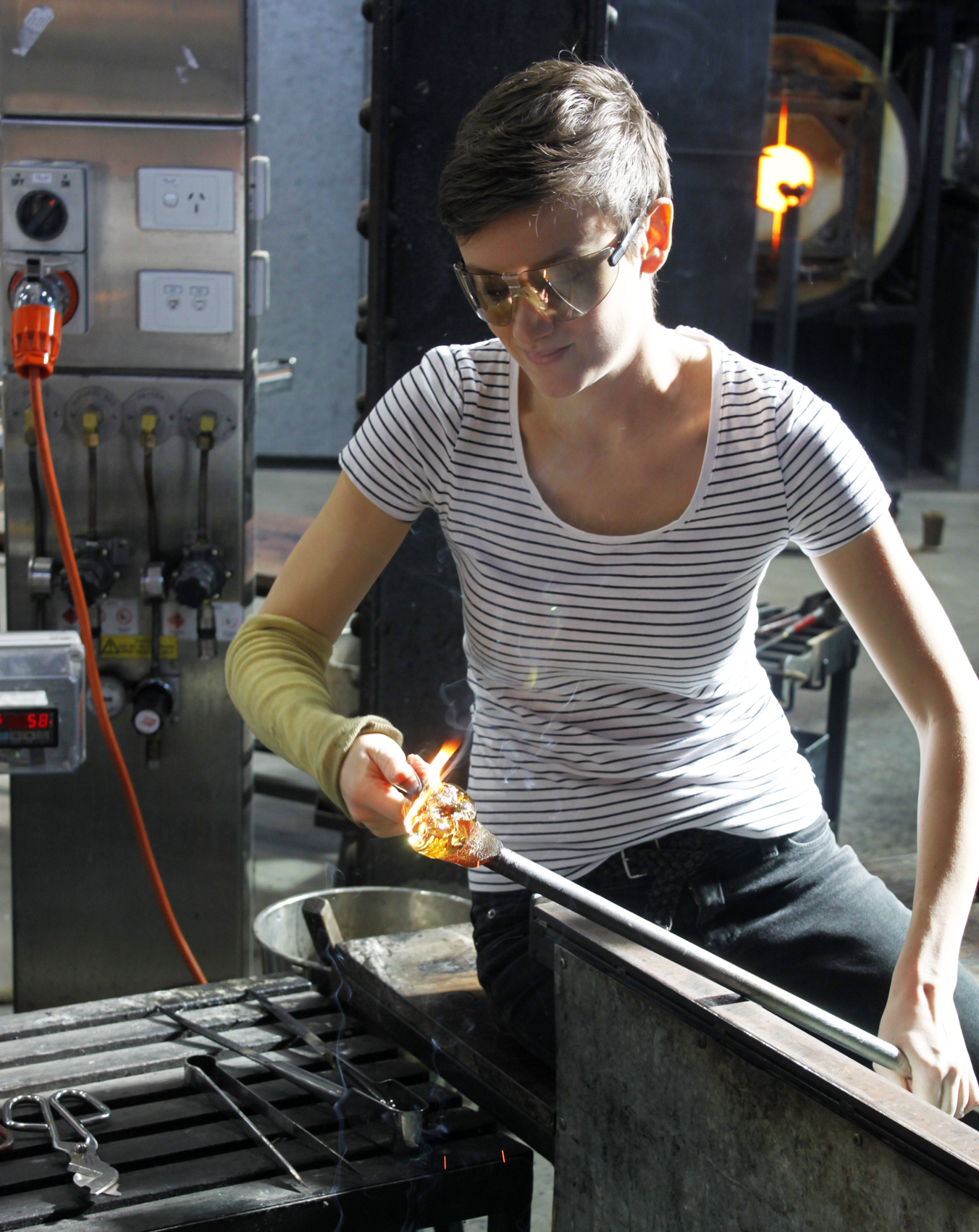 The dried wattle is being inserted and encased in the molten glass.