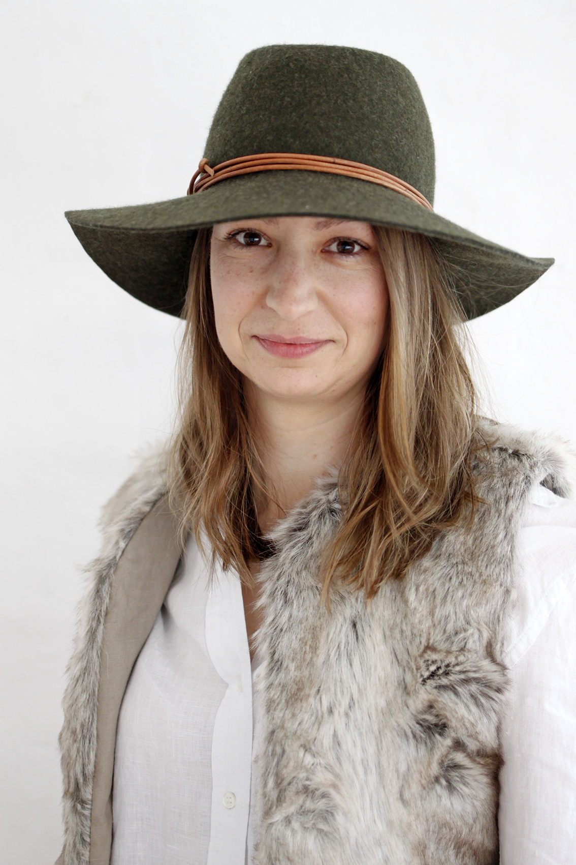 Felt Hat by  Fiona Schofield Millinery , Faux Fur Vest by  Tribe of Two Creative.