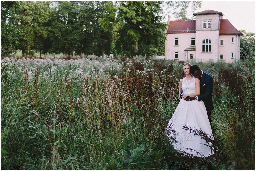 Das Brautpaar steht im hüfthohen Schilf und hält sich umarmt. Im Hintergrund steht ein schönes Gebäude.