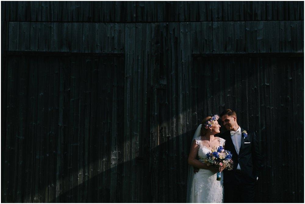 Brautpaar vor einer Holzhütte
