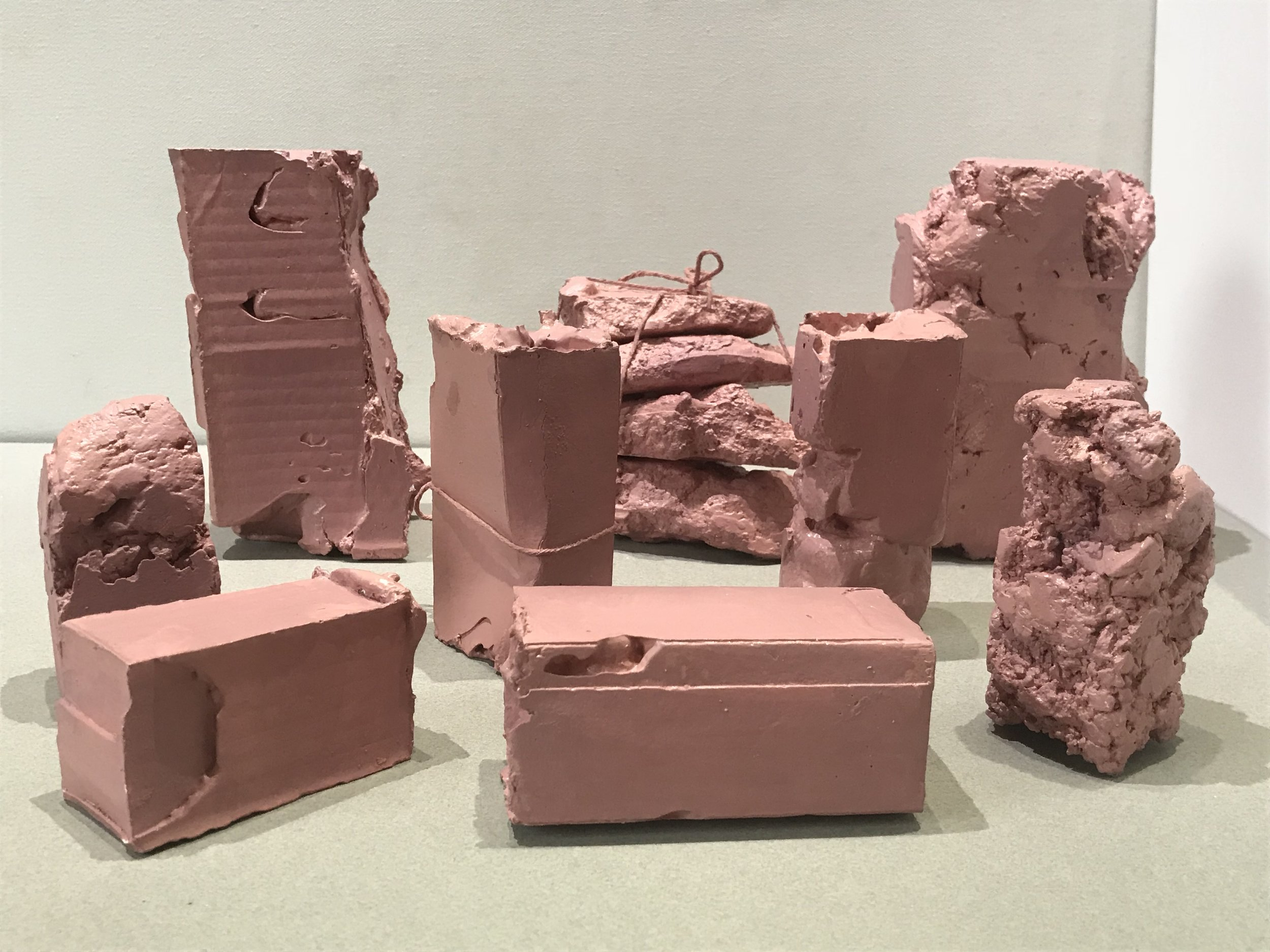 """Flesh Packages,  painted plaster, string collection of pieces each varying 6""""H X4""""W X 3""""L (2018)"""